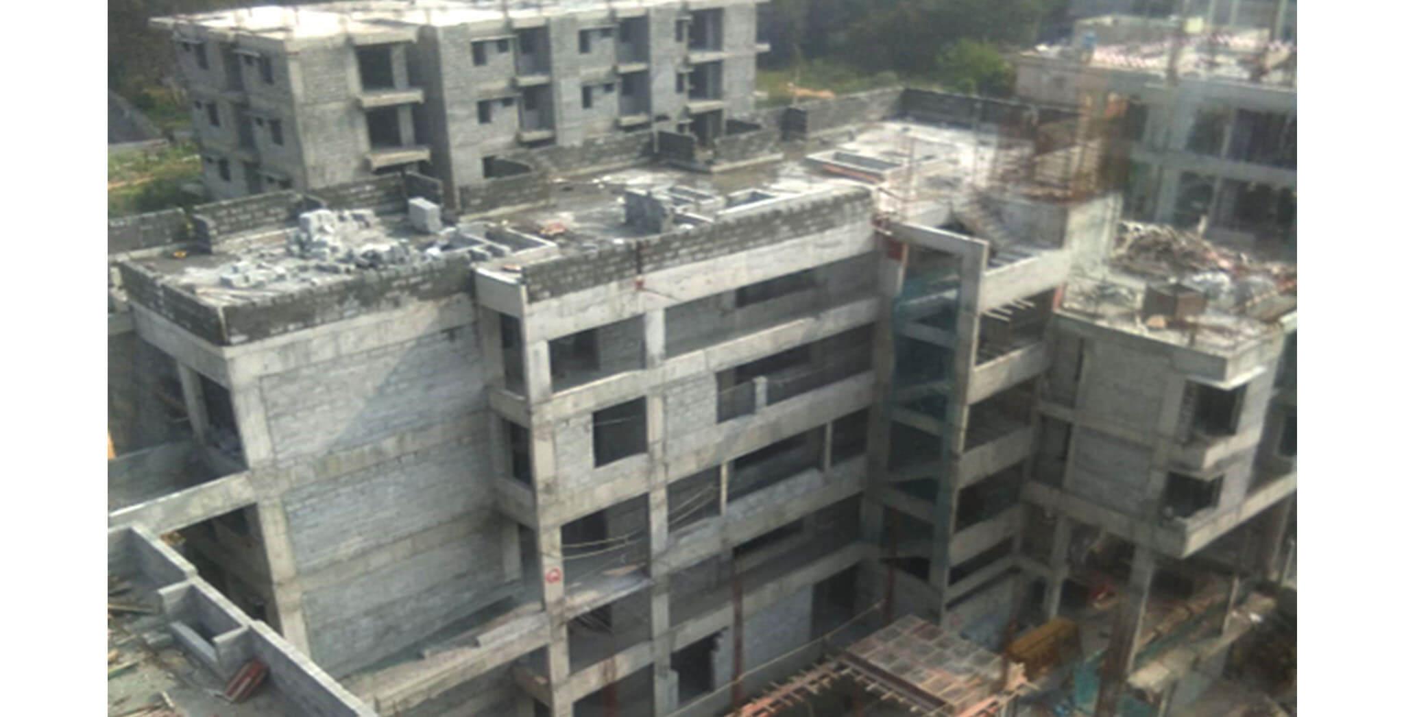 Oct 2020 - North side view: Q Block—internal plastering work-in-progress at 3rd floor level; Above terrace work-in-progress